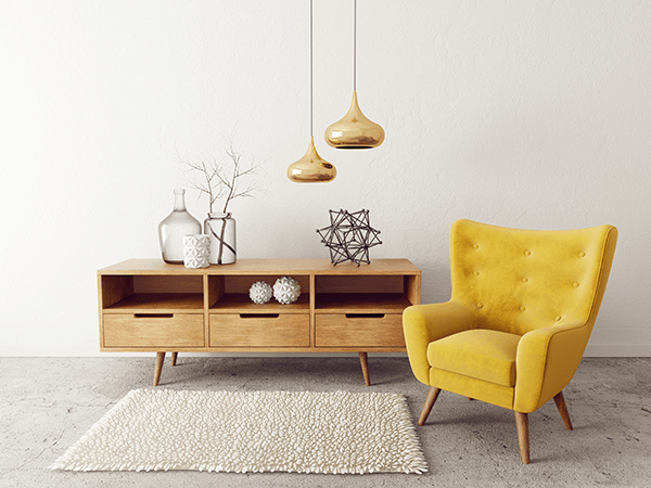 siting room area with gold hanging lamps, wood storage table, and modern yellow chair